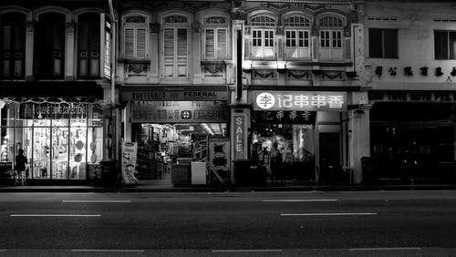 Grayscale Photo of Stores Near Road