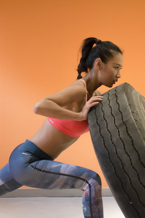 Woman Pushing Truck Tire