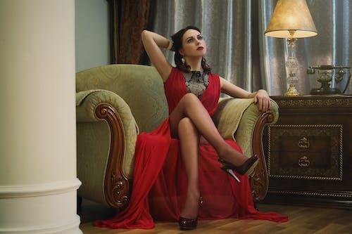 Woman Wearing Red Silt Dress Sitting on Beige Armchair
