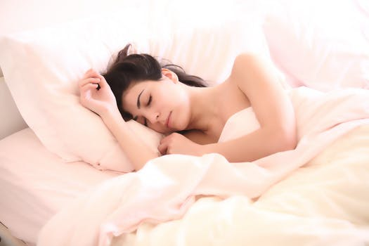 Woman Sleeping on Mattress Covered With Blanket