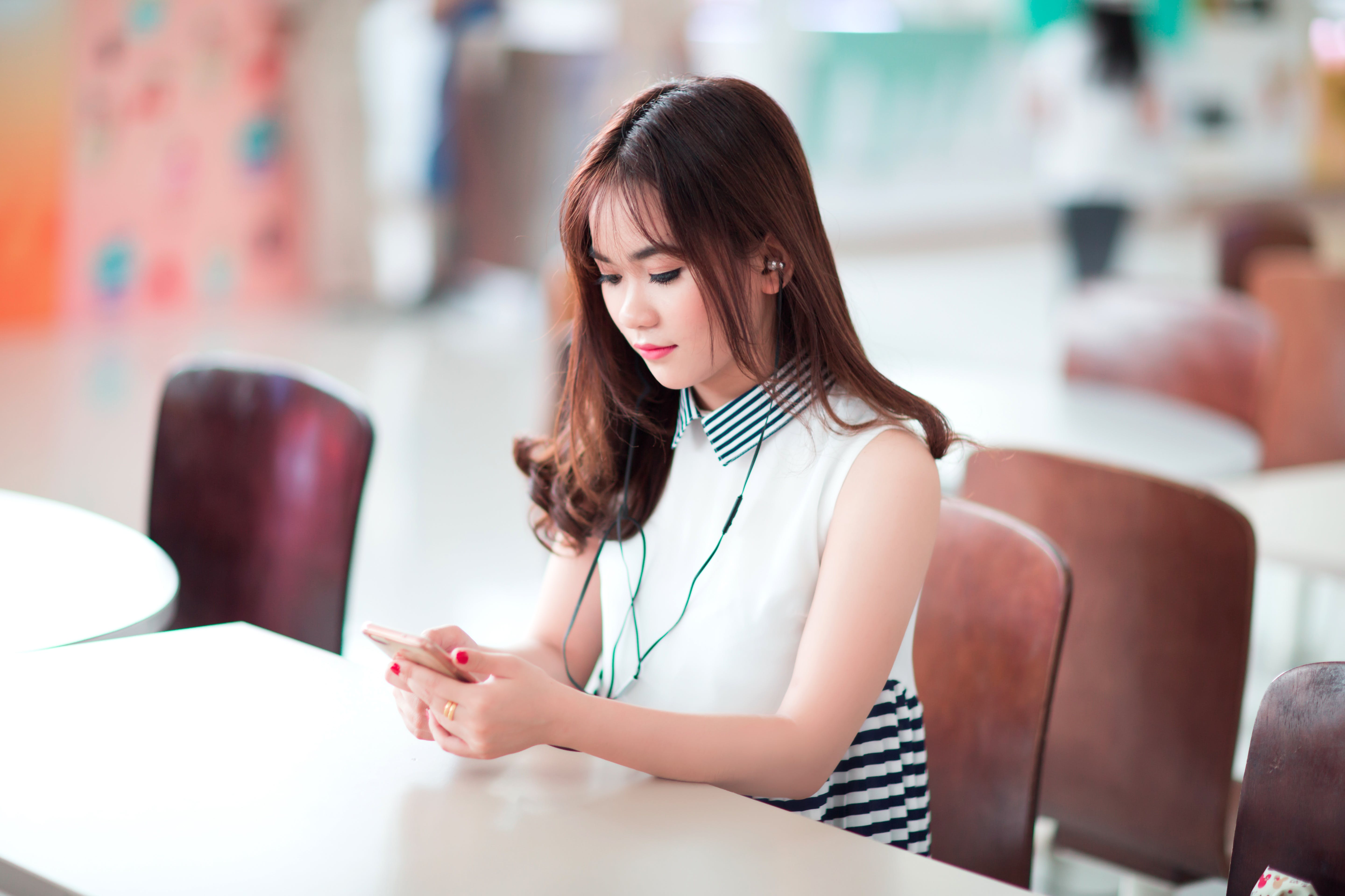Woman Sitting on Chair Holding Smartphone