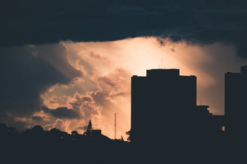 Silhouette of Building Under Cloudy Sky during Sunset
