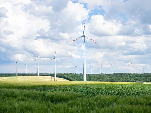 White Wind Turbines on Green Grass Field Under White Clouds and Blue Sky