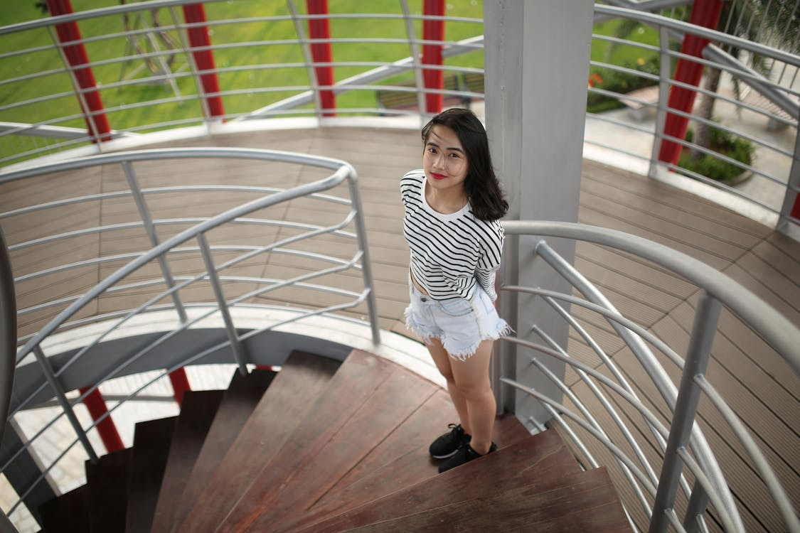 Woman Standing on Brown Wooden Spiral Staircase