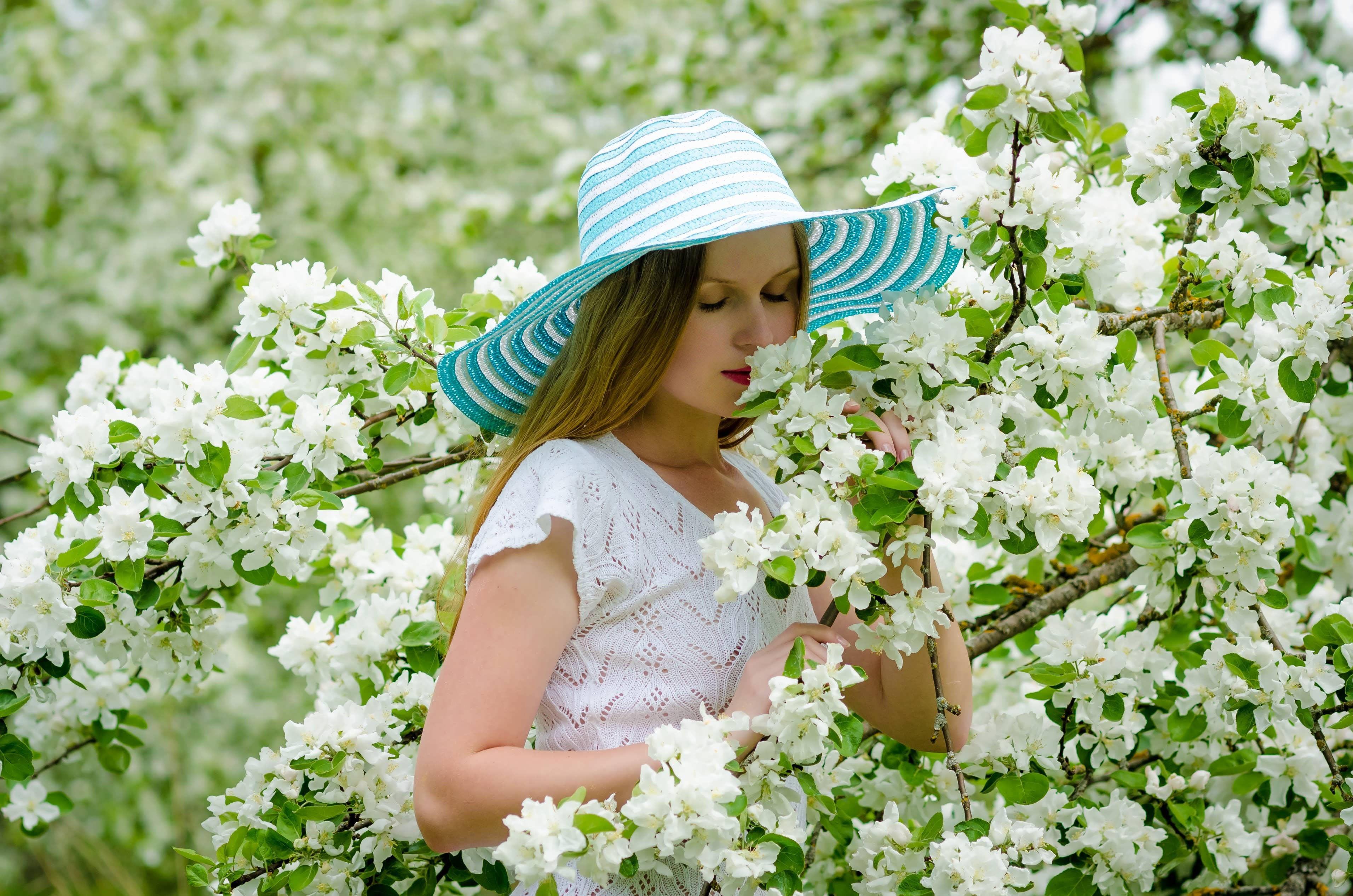 Woman Smells White Bougainvillea Flowers