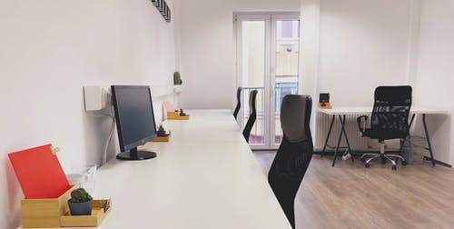 Black Office Rolling Chair Beside White Wooden Table