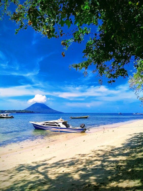 Boat Docked On Seashore Under Blue Sky