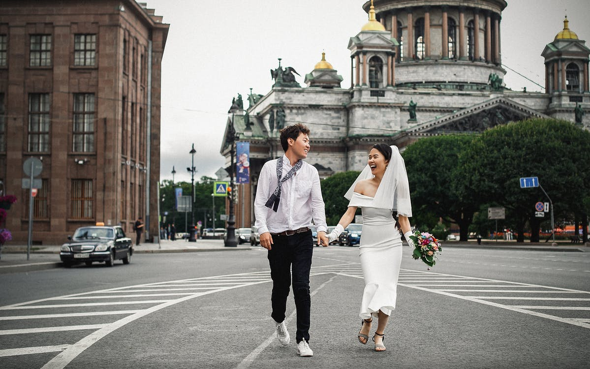 Man and Woman Holding Hands While Walking on Pedestrian Lane