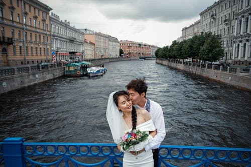 Couple Standing on Bridge wth Blue and White Boat on River