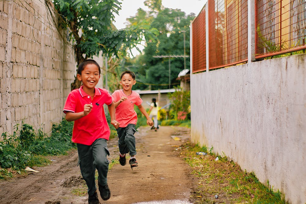Two little boys running on alley. | Photo: Pexels