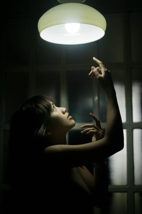 어두운 방에서 전기 램프에 팔을 올리는 화려한 여자