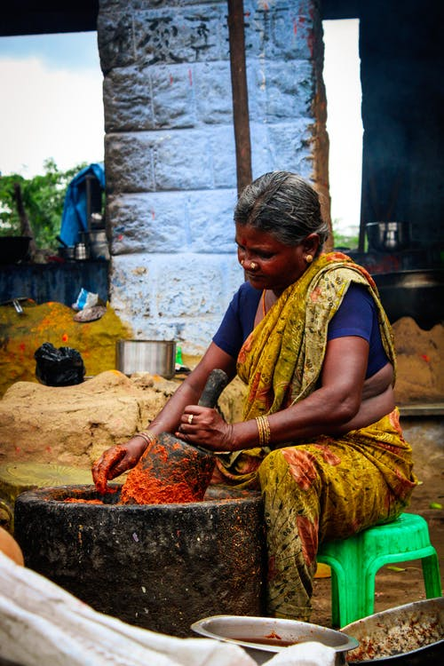 Indian woman powdering spices in big stone bowl