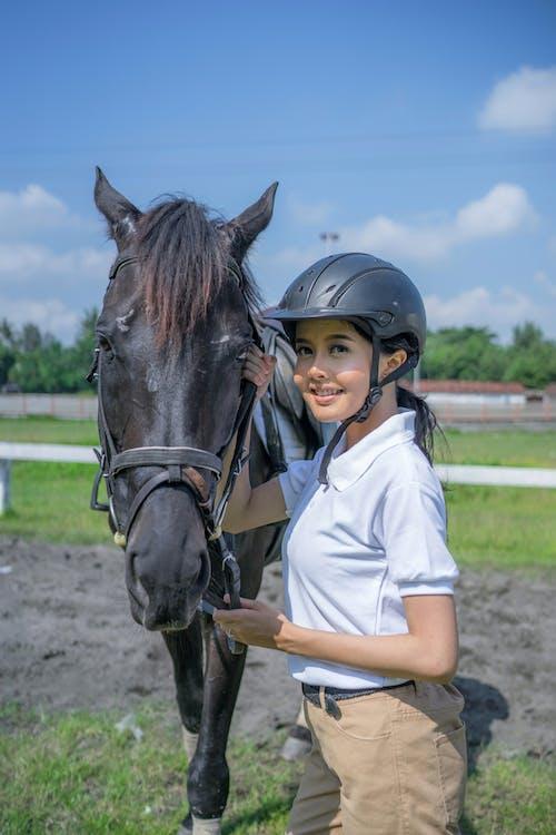 Woman in White Shirt Riding Black Horse