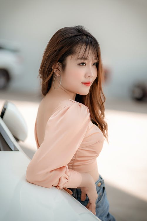 Positive Asian woman leaning on white car on street