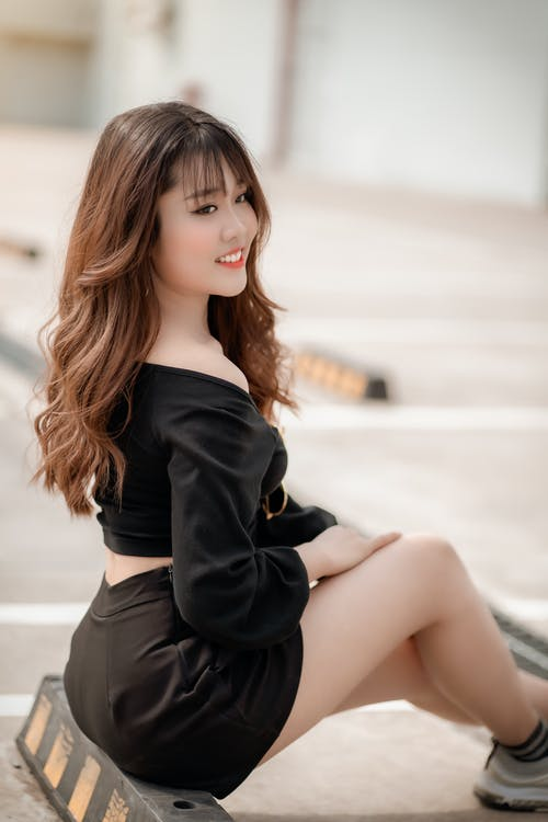 Woman in Black Long Sleeved Top and a Black Short Skirt Sitting on Black Wooden Bench