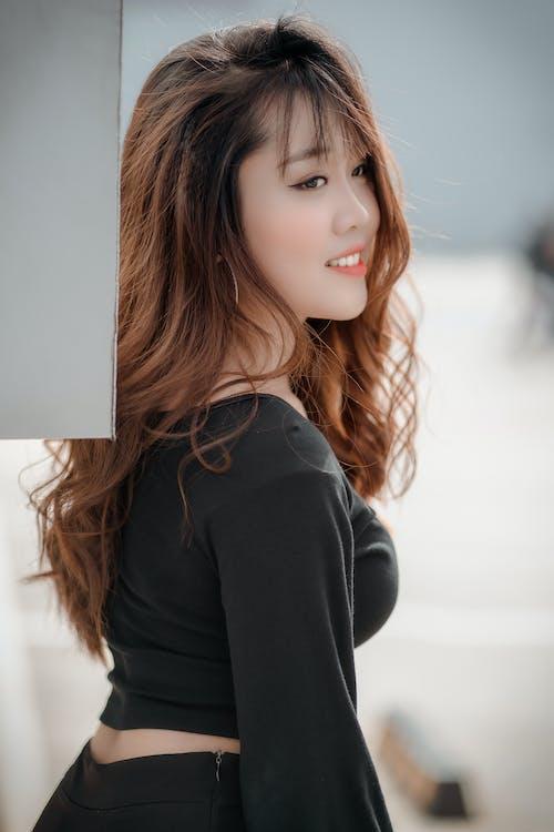 站立在演播室的時髦的亞裔婦女
