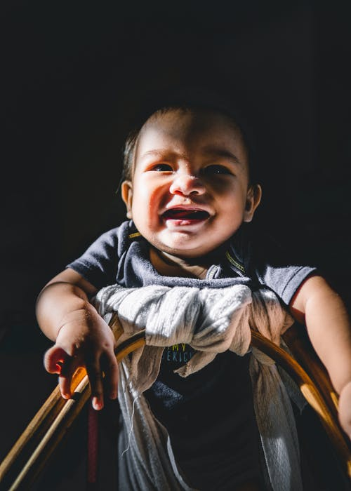 Happy ethnic infant in baby walker