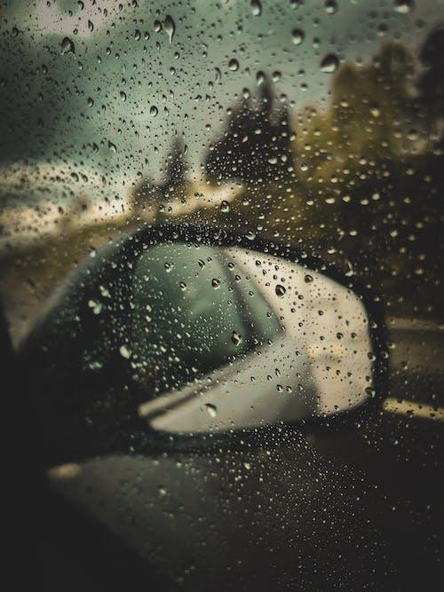 Car viewing mirror through window during rain
