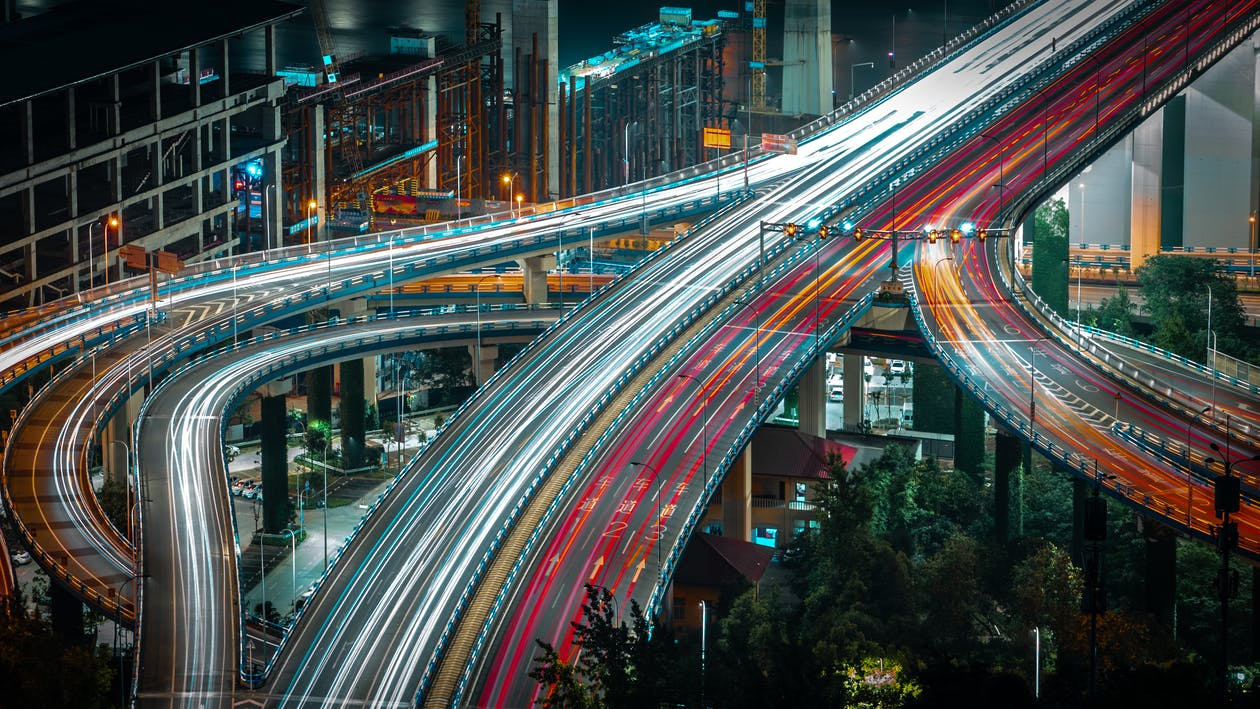 From above long exposure traffic on modern highway elevated above ground level surrounded by urban constructions in evening