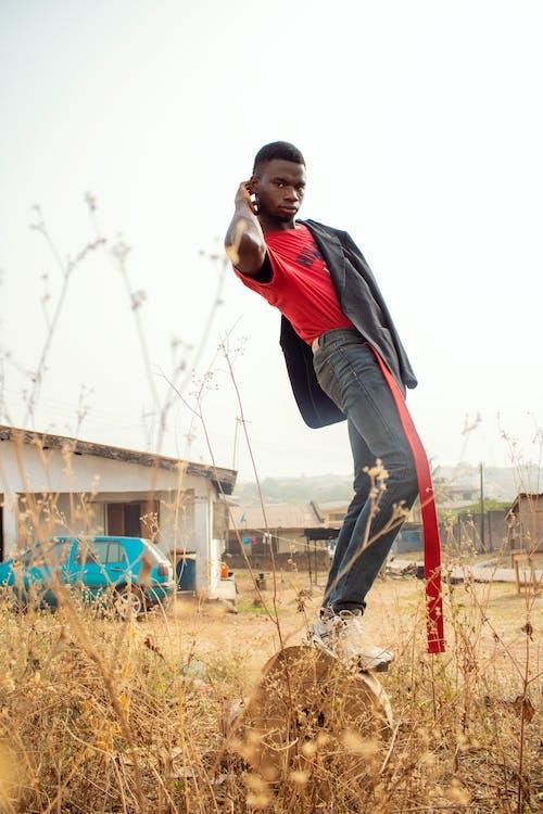 Calm stylish black man standing on haymow on farm