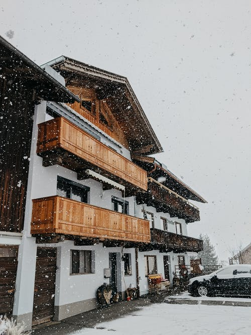 Cozy cottage in winter during snowfall