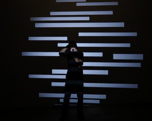 силуэт человека, стоящего перед сине белой полосатой стеной