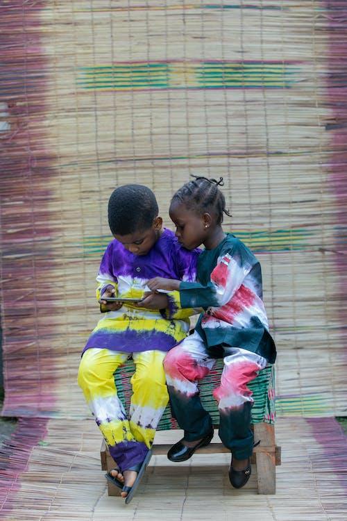 Black children sitting on stool and using smartphone