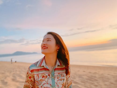 Woman in White Red and Blue Floral Button Up Shirt Standing on Brown Sand Looking Away