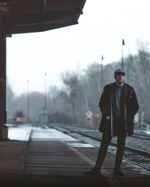 Unemotional man standing on railroad station platform on winter day