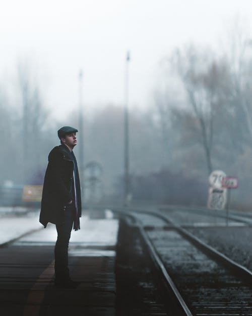 Calm man waiting for train on railroad platform in winter