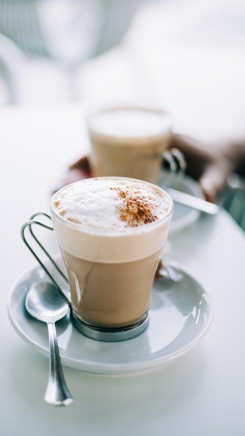 Tazza In Vetro Trasparente Con Cappuccino Su Piattino In Ceramica Bianca