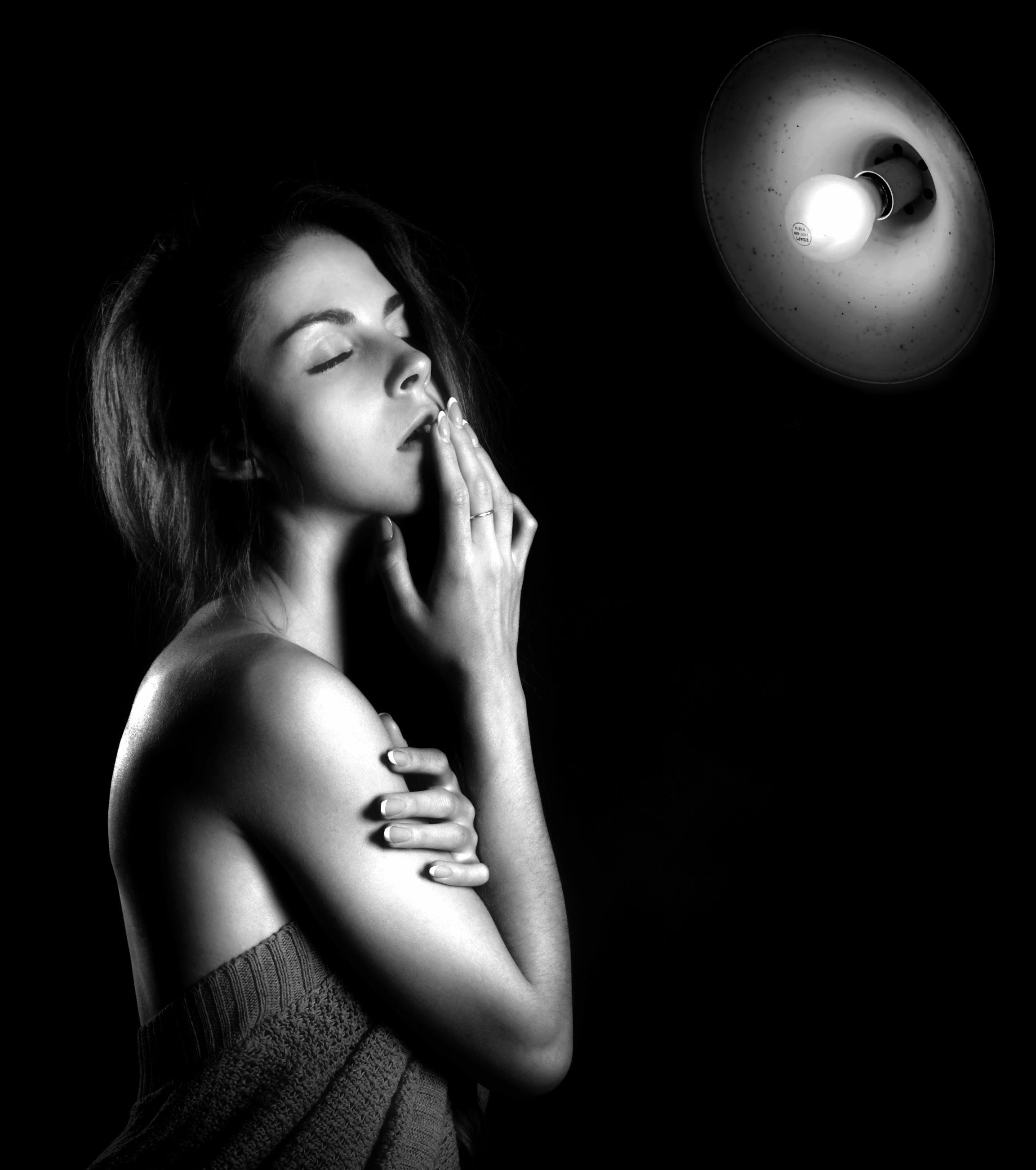 Grayscale Photography of Woman Holding Her Mouth in Front of Bulb Light