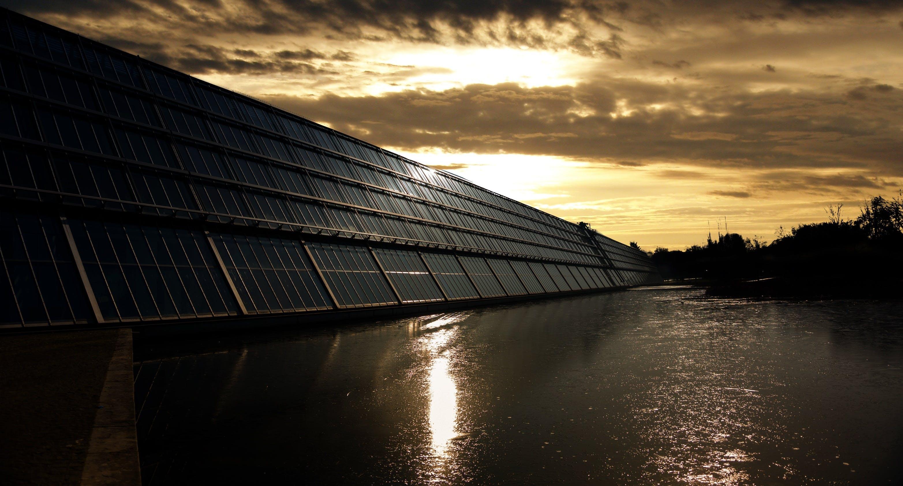 Black Solar Panel Near Calm Body of Water