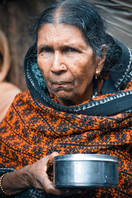 Senior Asian female in authentic national clothes with steel bowl standing on street market and looking at camera