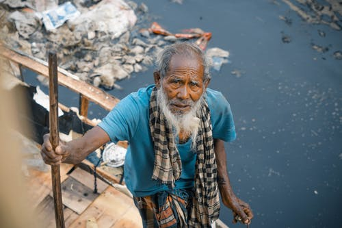 From above cheerless elderly Asian male in worn out clothes standing near dirty polluted river full of rubbish in poor district and looking at camera