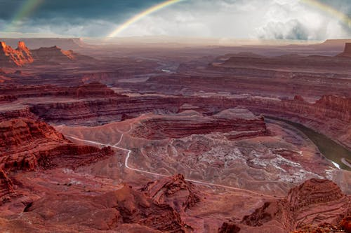 Amazing view of scenic canyon with red colored rock formations and narrow curvy river under blue sky with picturesque rainbow