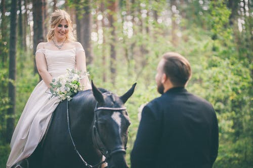 Woman in White Dress on Black Horse Looking at Man in Black