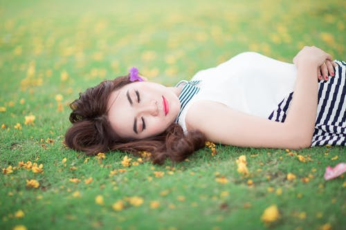 Selective Focus Photography of Woman Lying on Grass Field