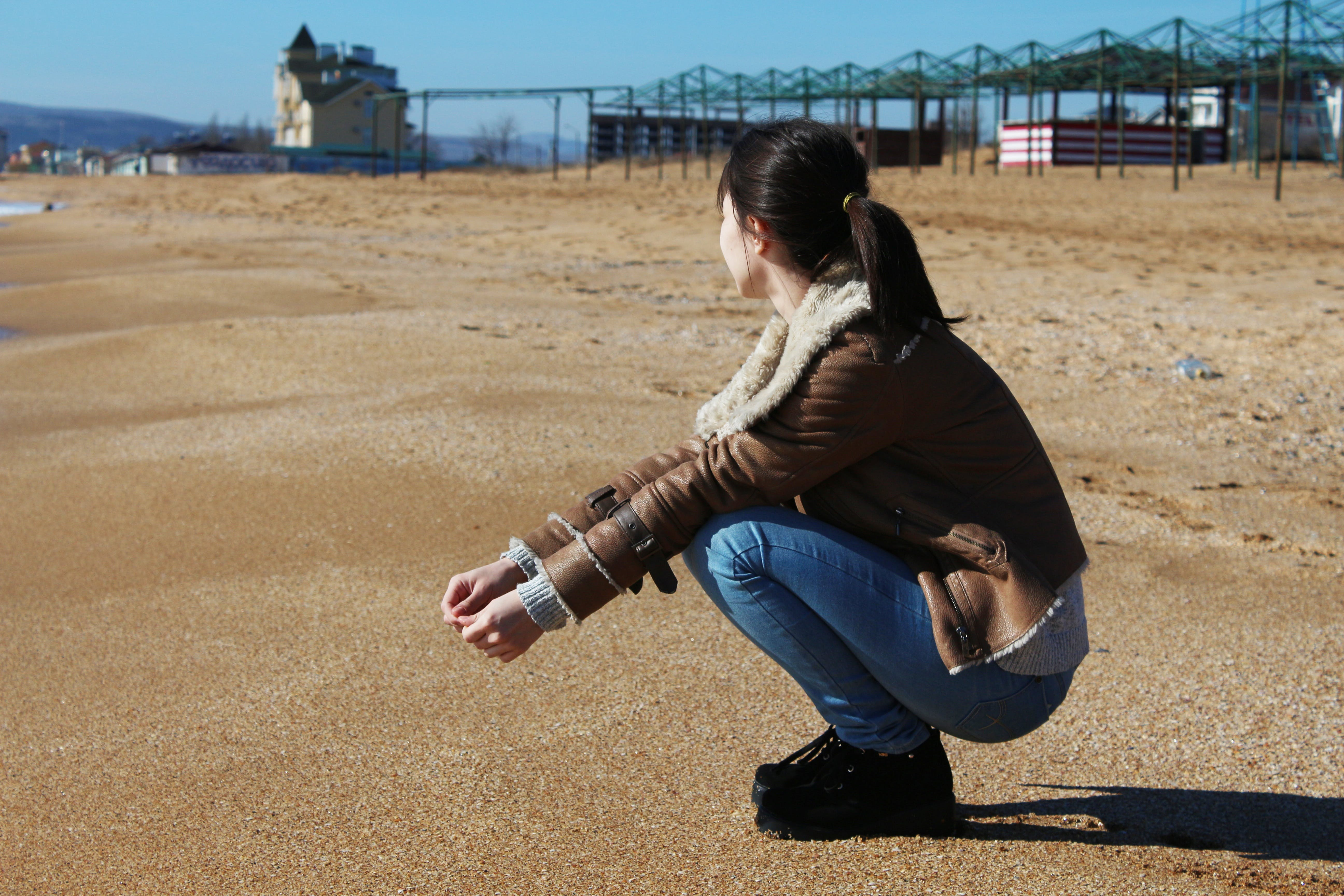 Woman Crouching on Brown Sand
