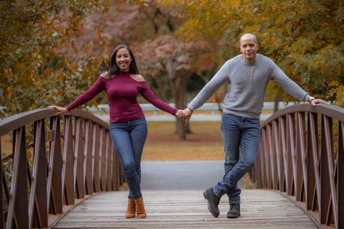 Man and Woman in Denim Jeans Holding Hands  on Wooden Bridge