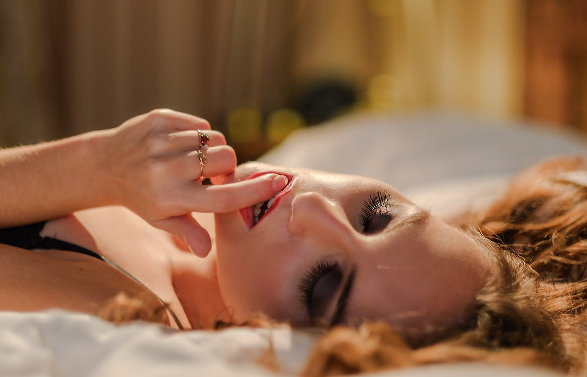 Woman Holding Her Lips Lying on White Surface