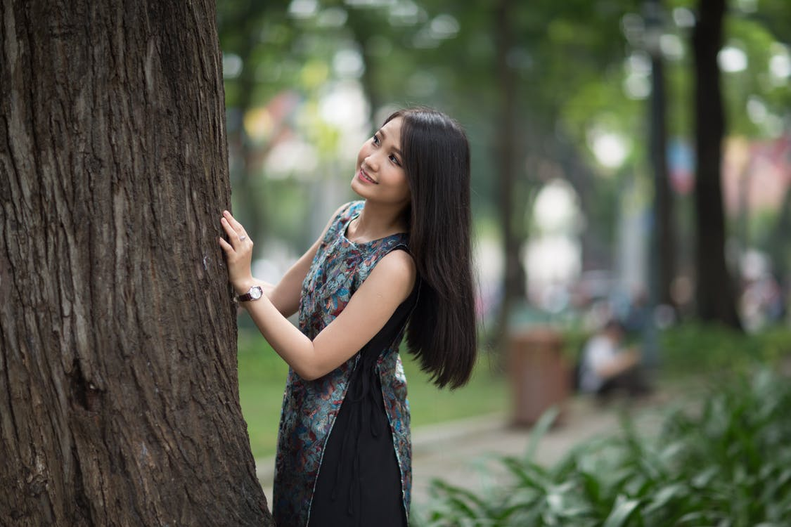 Smiling Woman in Front of Tree Trunk