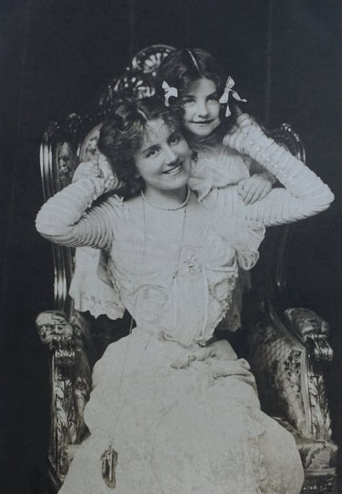 Classic Photo Of Smiling Mother And Daughter Sitting On An Armchair