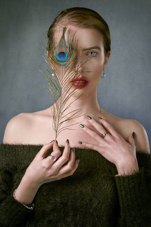 Unemotional young female model wearing cozy dark green sweater with open shoulders covering face with colorful bright peacock feather and looking at camera sensually