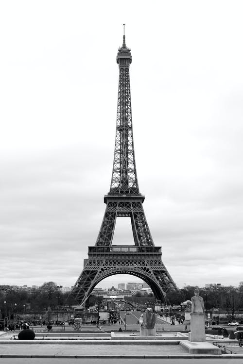 Black and white majestic famous Eiffel Tower against Elysian Fields on summer day