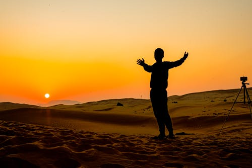 Silhouette of man with photo camera in desert