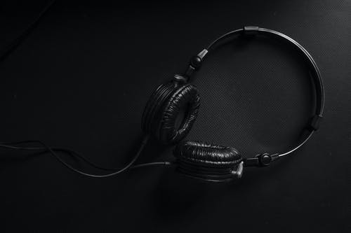 Black and Silver Headphones on Black Surface