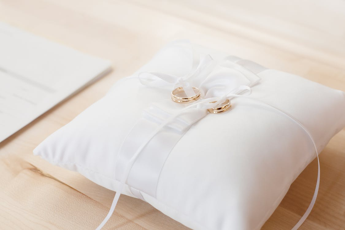 Closeup Photo of Pair of Gold Bridal Rings on Top of White Pillow