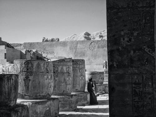 Foto Grayscale Pria Berdiri Dekat Gedung Beton