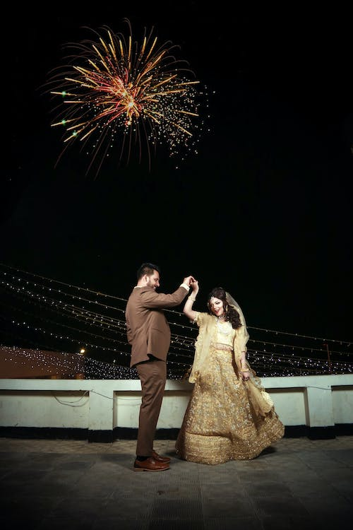 Man and Woman Dancing on White Concrete Bridge during Night Time